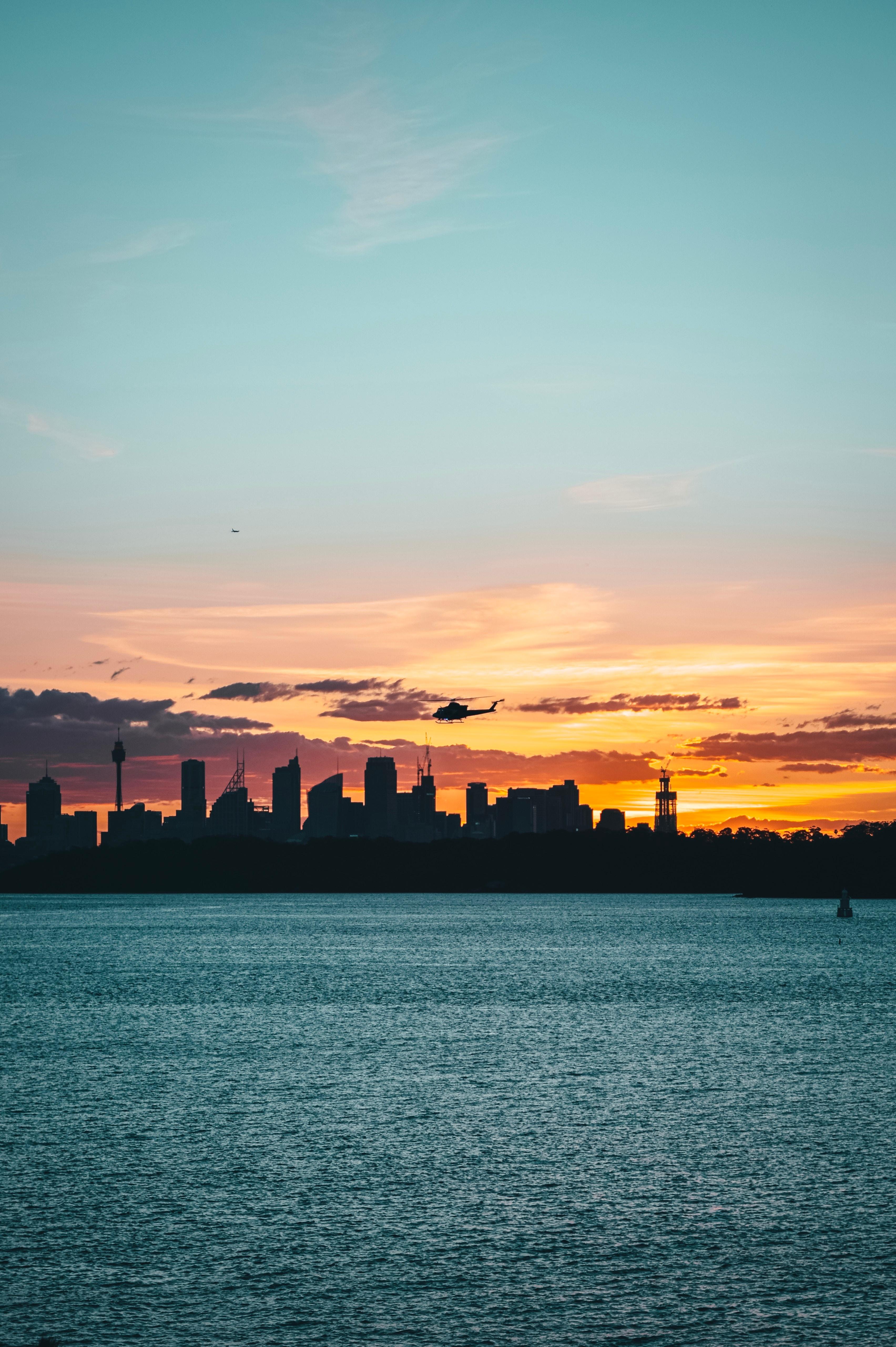 53562 Hintergrundbild herunterladen Städte, Hubschrauber, Stadt, Gebäude, Dunkel, Küste, Dämmerung, Twilight - Bildschirmschoner und Bilder kostenlos