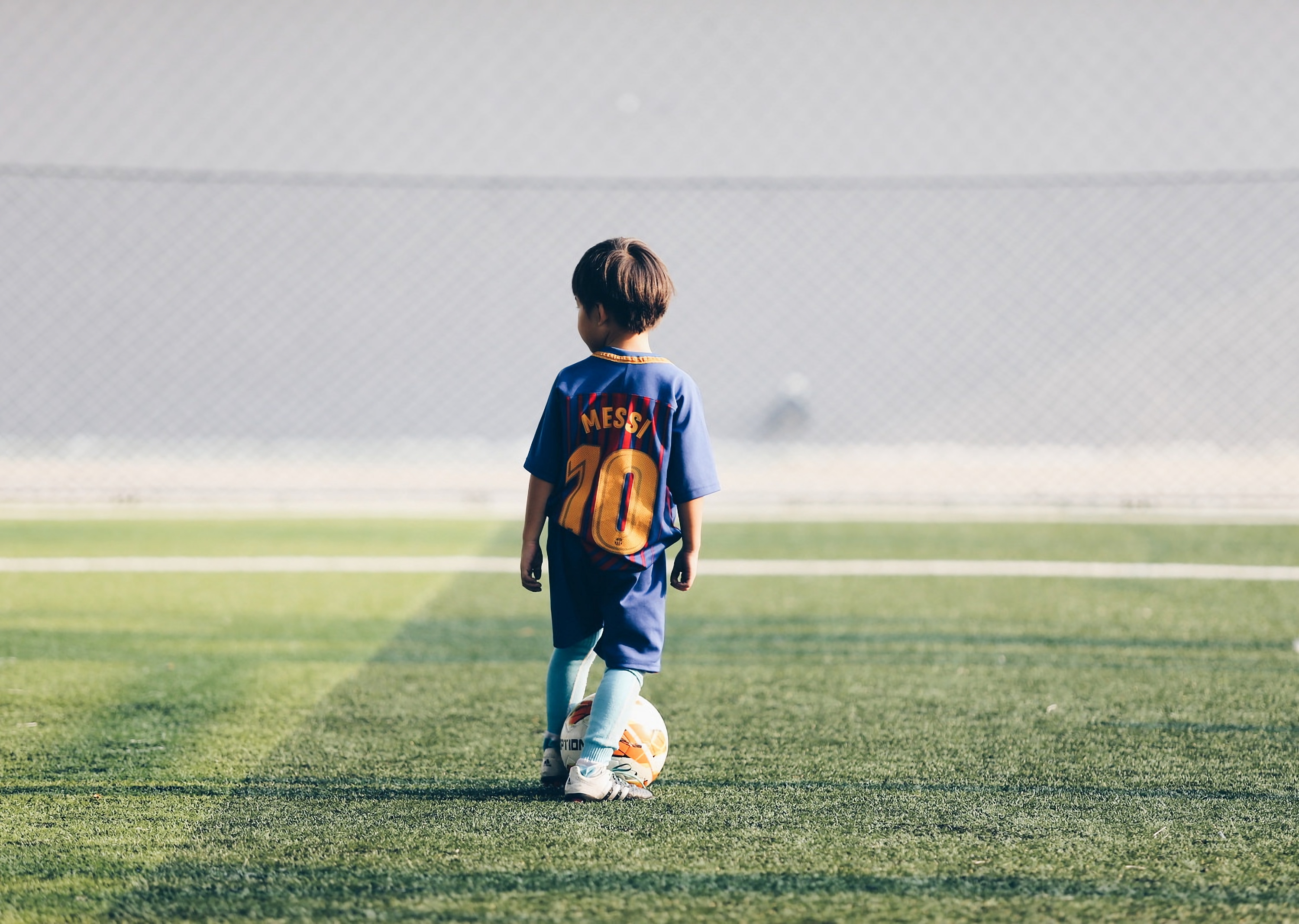 94777 download wallpaper Sports, Child, Footballer, Football, Football Field, Ball, Lawn screensavers and pictures for free