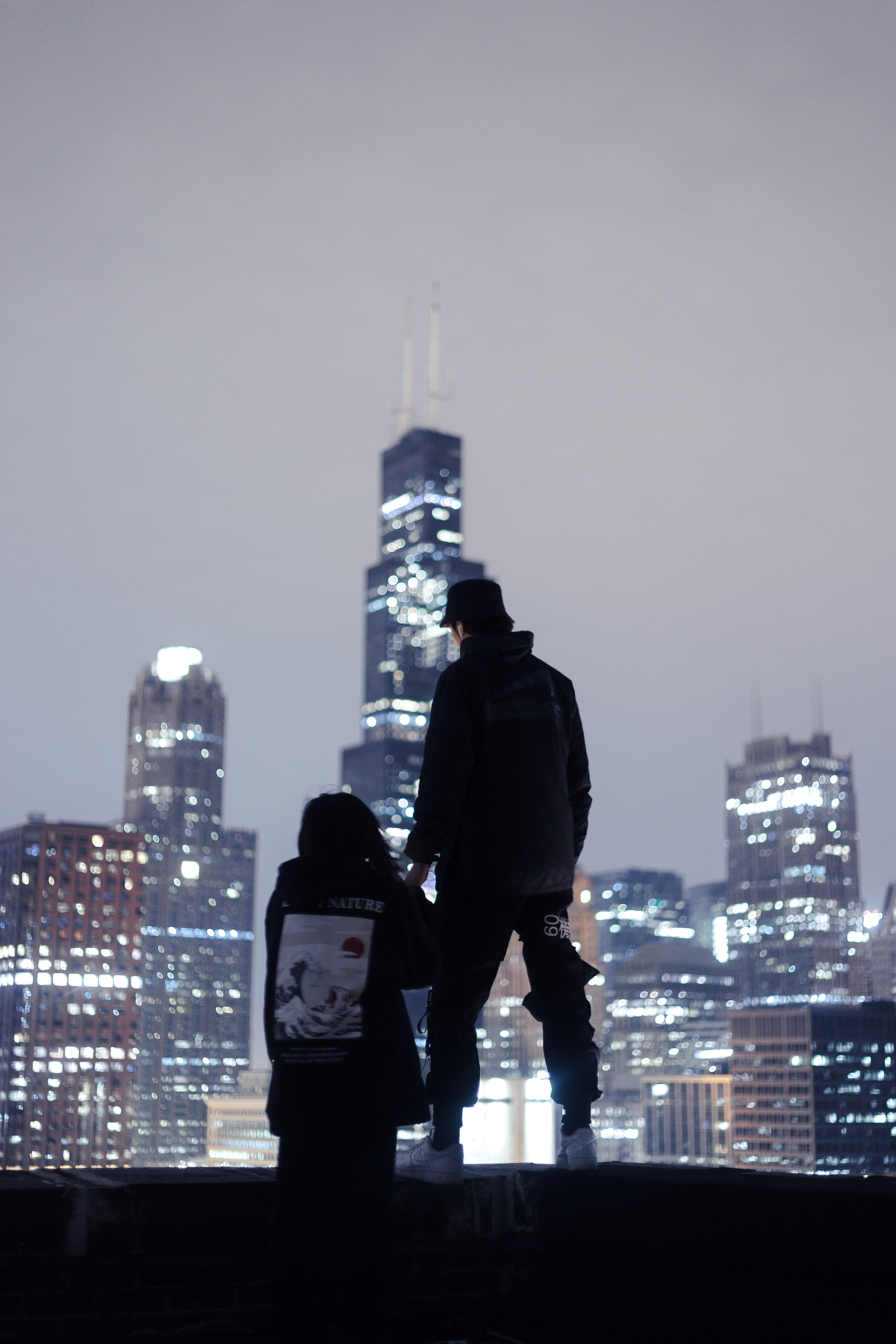 126396 download wallpaper Dark, Couple, Pair, Roof, Love, Night City, Skyscrapers, Overview, Review screensavers and pictures for free