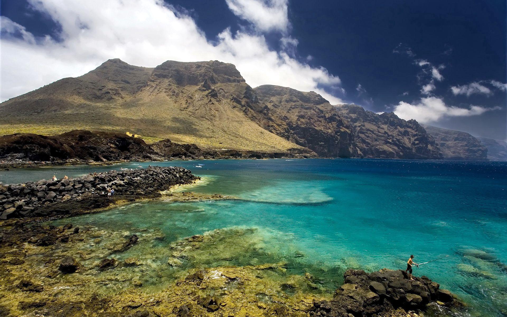 94917 скачать обои Природа, Тенериф, Испания, Залив, Камни, Рыбак, Небо, Облака, Ясно, Горы - заставки и картинки бесплатно
