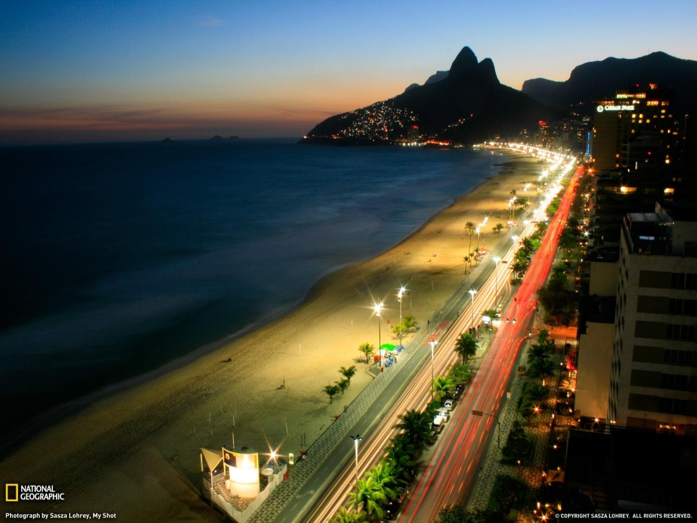 Скачать картинку Пейзаж, Города, Дороги, Горы, Море, Ночь, Пляж в телефон бесплатно.