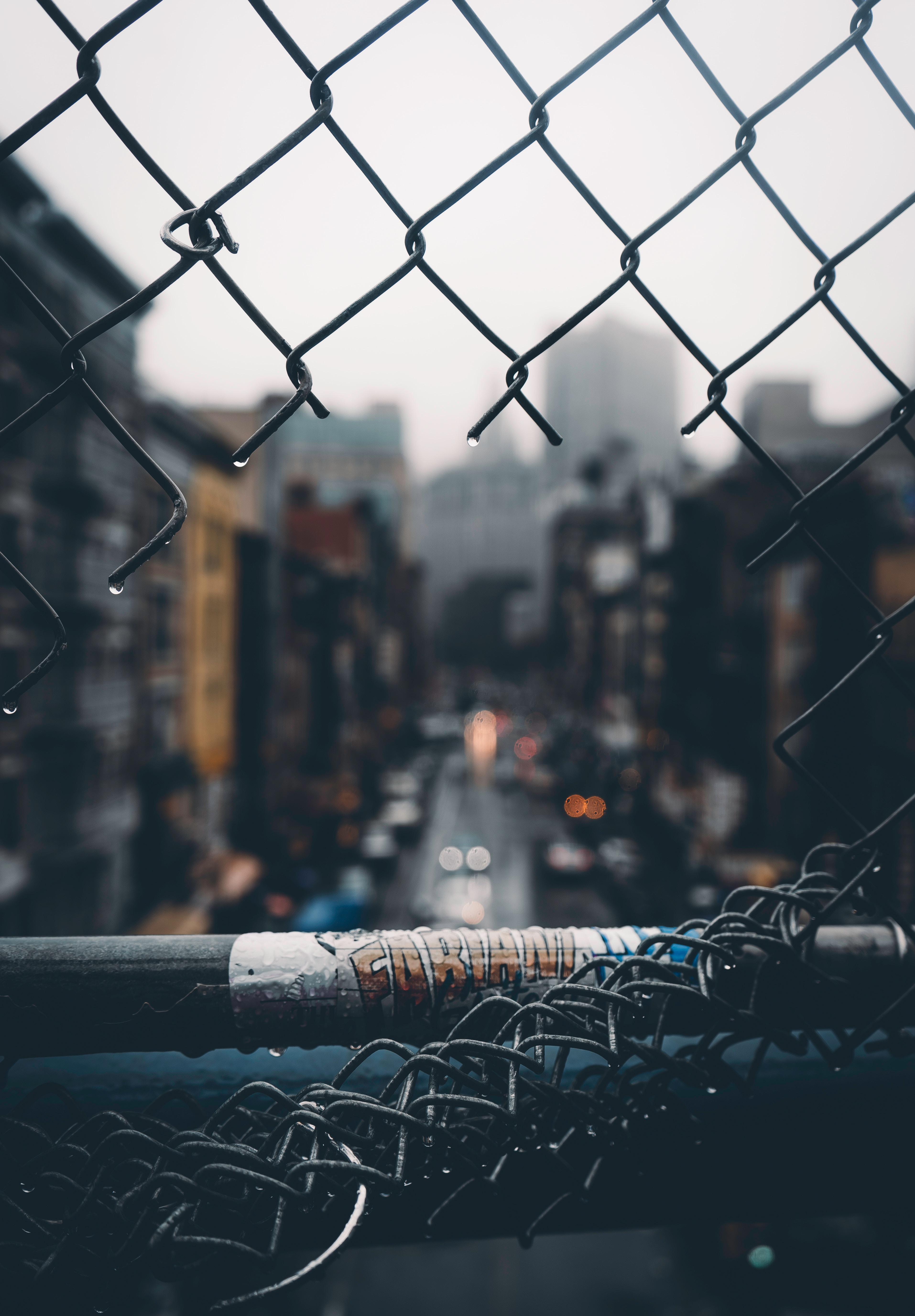 127052 download wallpaper Miscellanea, Miscellaneous, Fence, Grid, Hole, Rain, City, Blur, Smooth screensavers and pictures for free