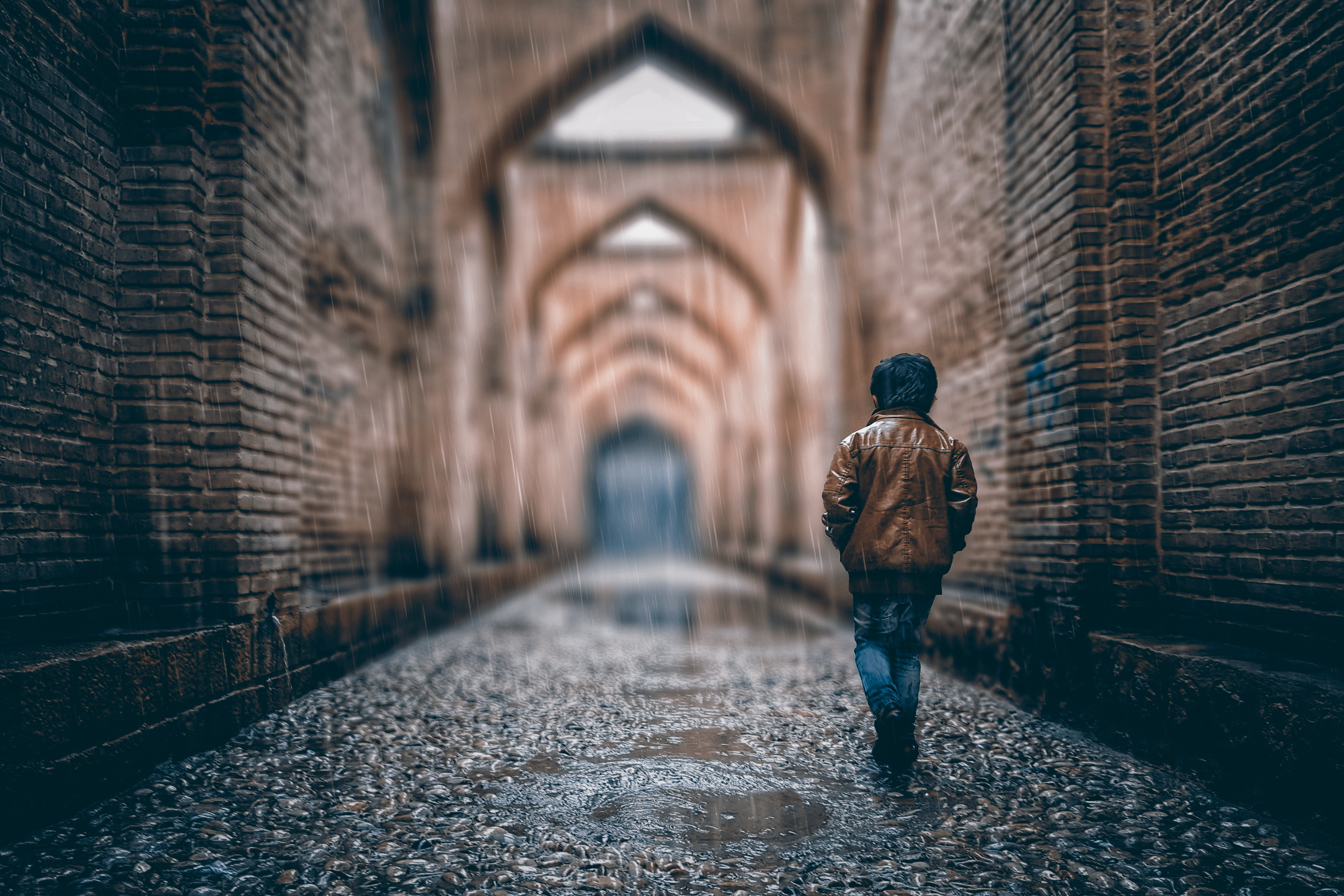 113751 download wallpaper Rain, Walls, Miscellanea, Miscellaneous, Stone, Arch, Street, Arches, Boy screensavers and pictures for free