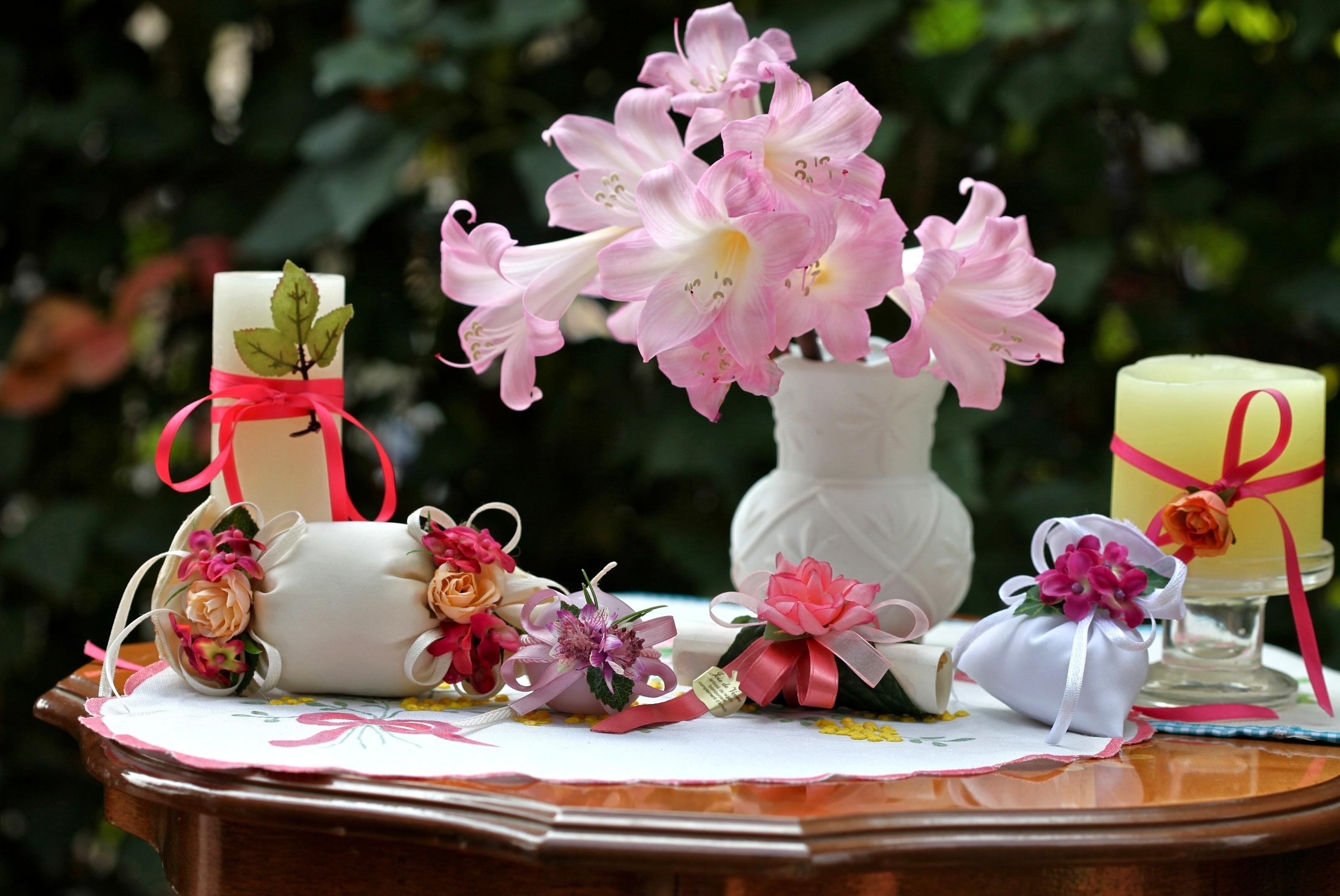 108592 download wallpaper Flowers, Vase, Pouches, Bags, Bows, Candles, Table, Roses screensavers and pictures for free