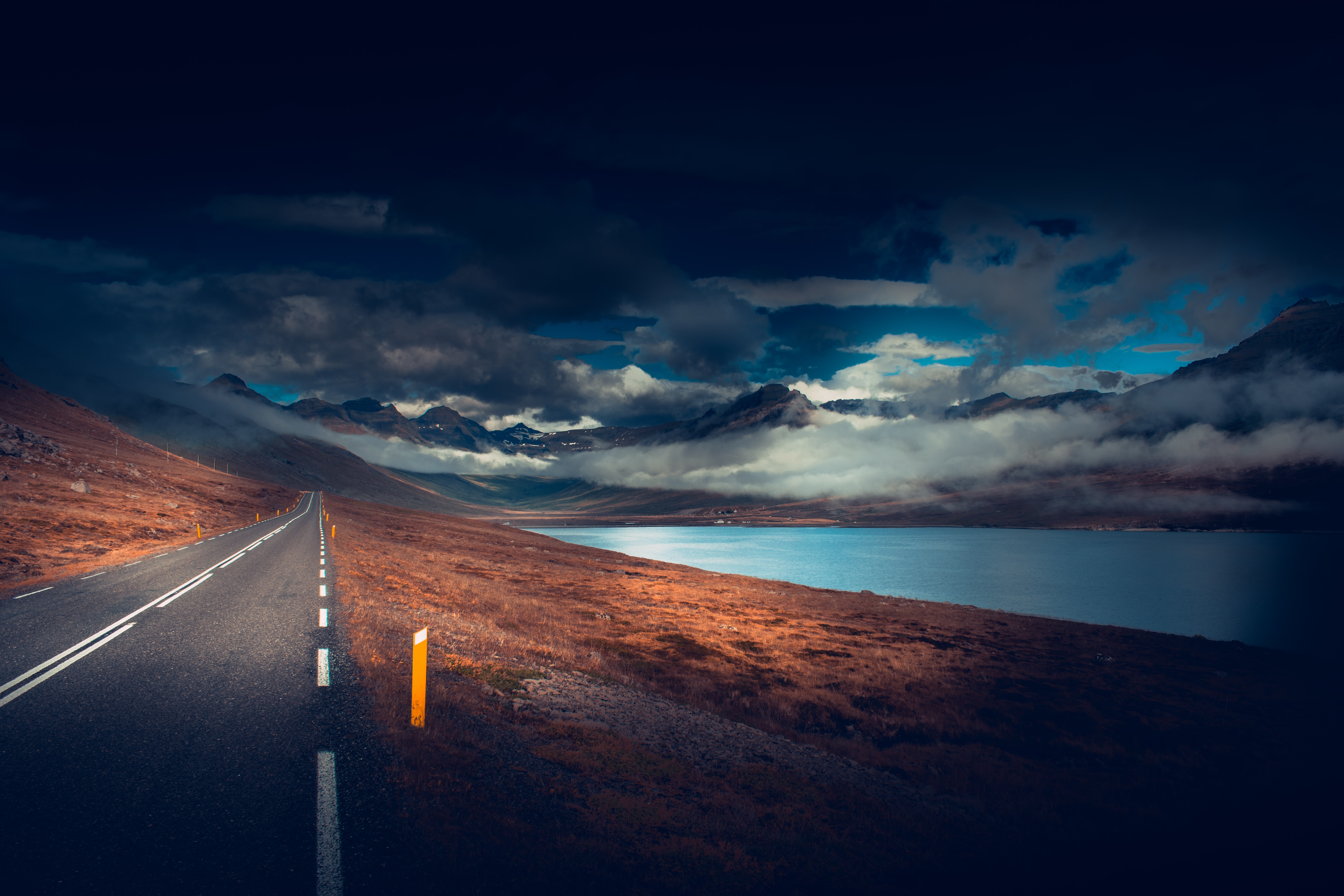 Free wallpaper 117986: Nature, Road, Asphalt, Markup, Lake, Dark, Clouds, Mountains download pictures for cellphone