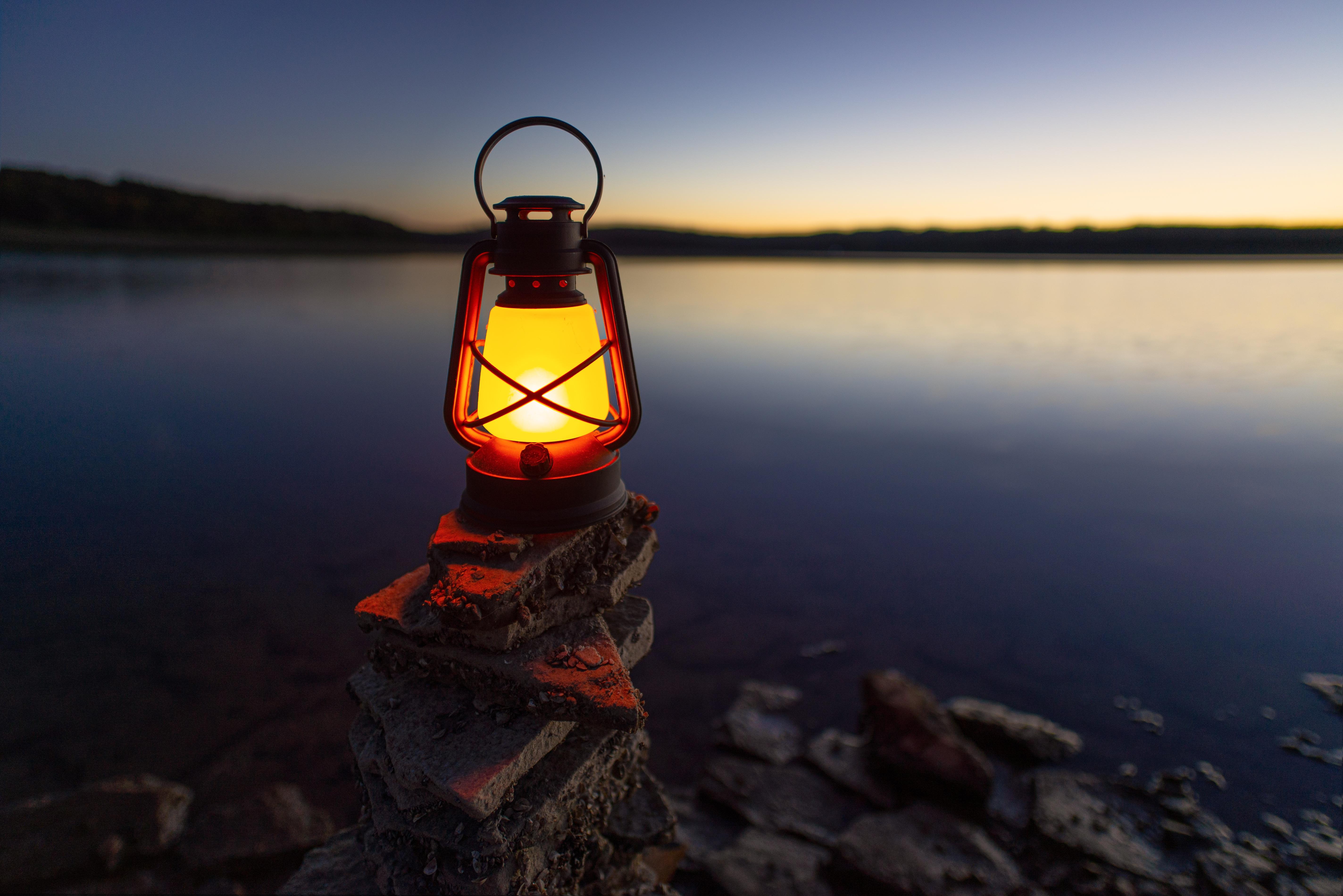 141442 download wallpaper Dark, Lamp, Lantern, Shine, Light, Stones, Lake, Shore, Bank screensavers and pictures for free