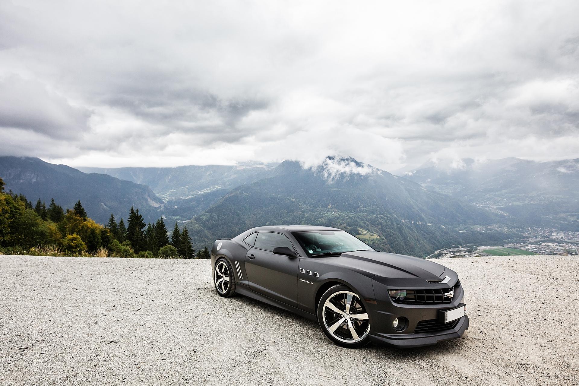 80216 скачать обои Тачки (Cars), Шевроле (Chevrolet), Camaro Ss, Шевроле, Камаро Сс, Чёрный, Небо, Тучи, Горы - заставки и картинки бесплатно