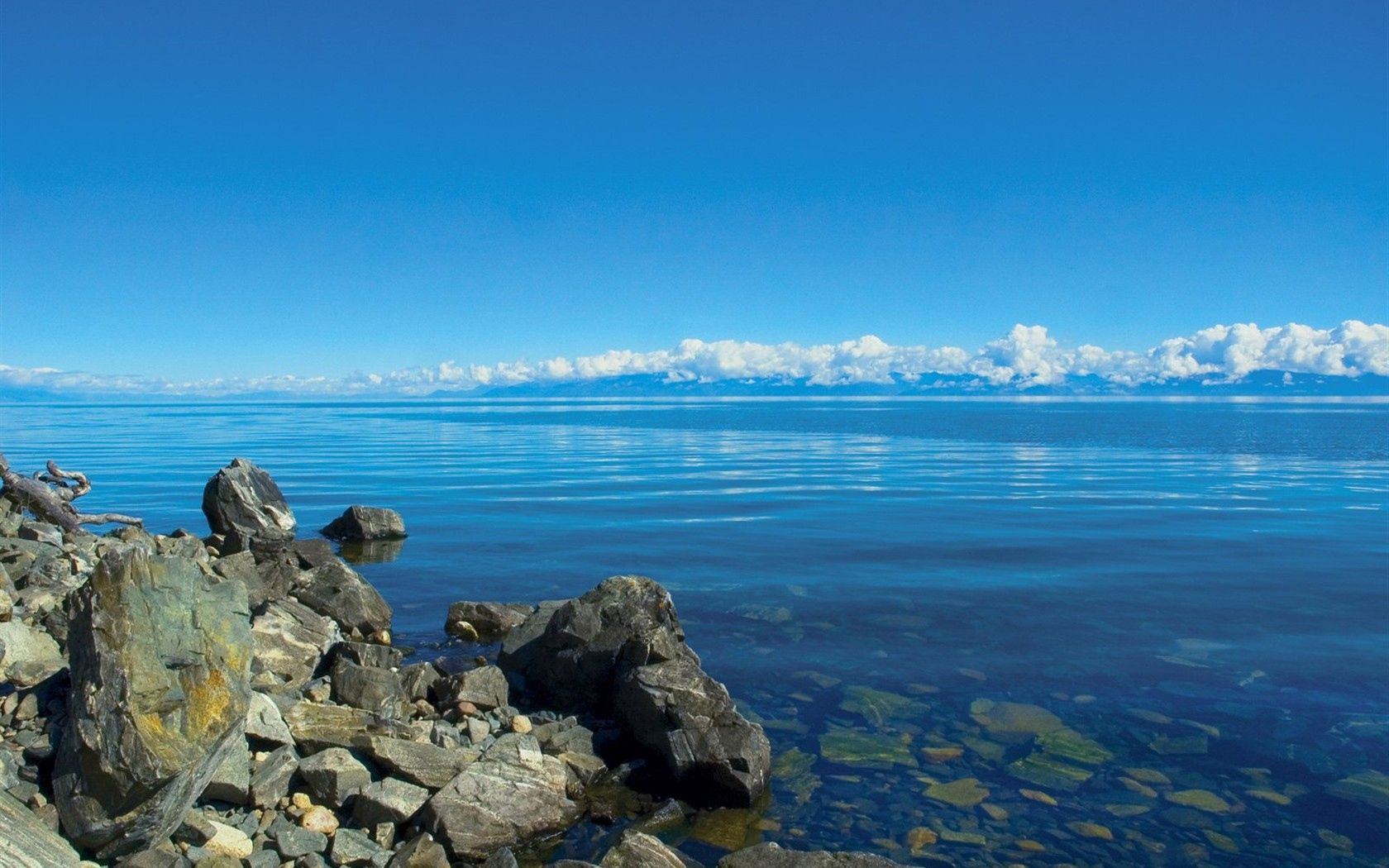 56224 download wallpaper Nature, Water, Stones, Clouds, Lake, Transparent, Siberia, Baikal screensavers and pictures for free