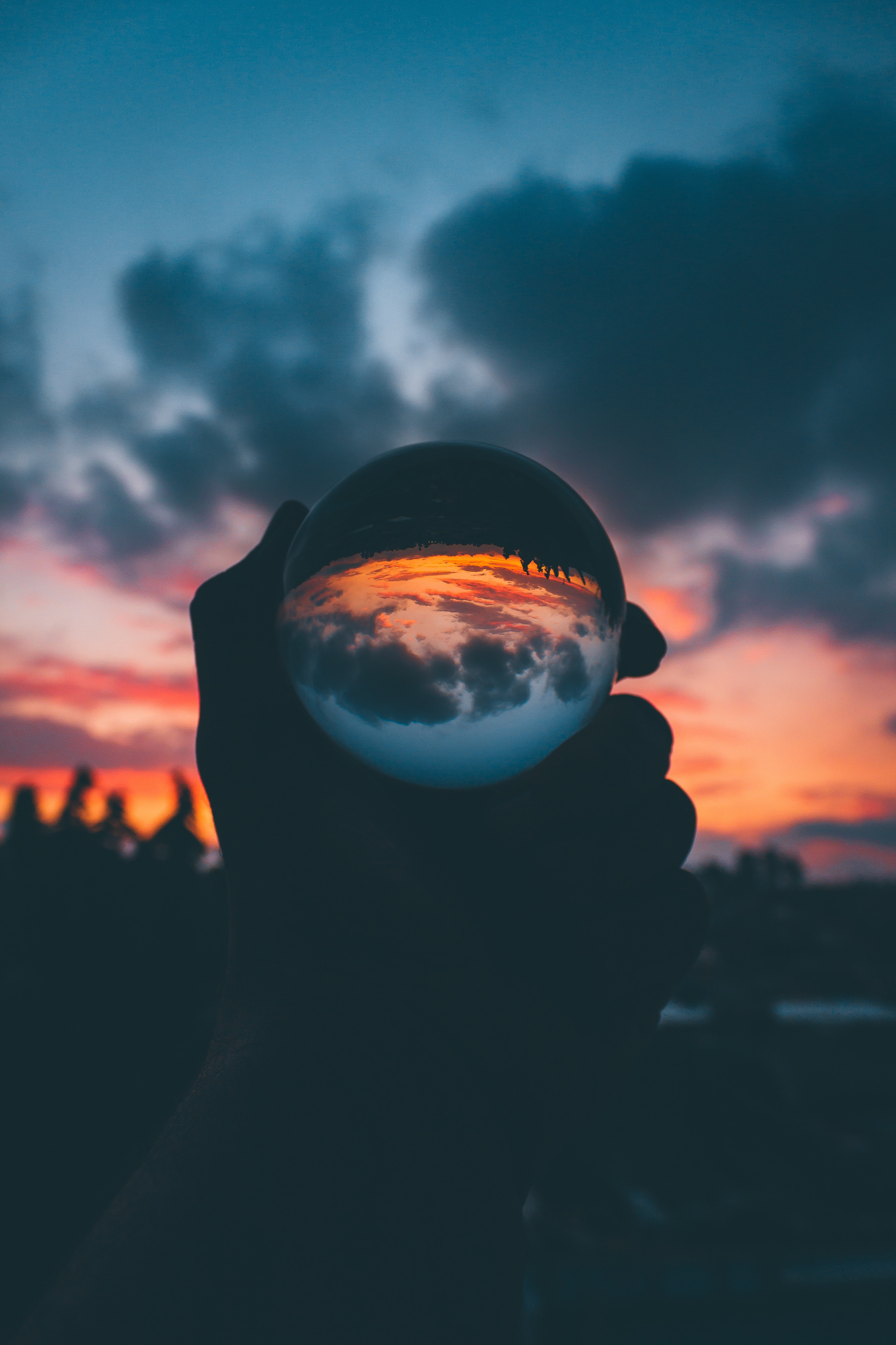 142987 download wallpaper Glass, Sunset, Reflection, Dark, Hand, Ball screensavers and pictures for free